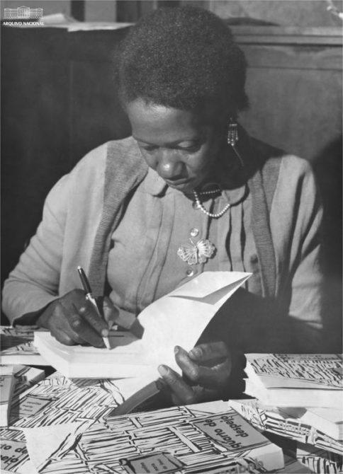 Carolina Maria de Jesus assinando seu livro Quarto de Despejo em 1960